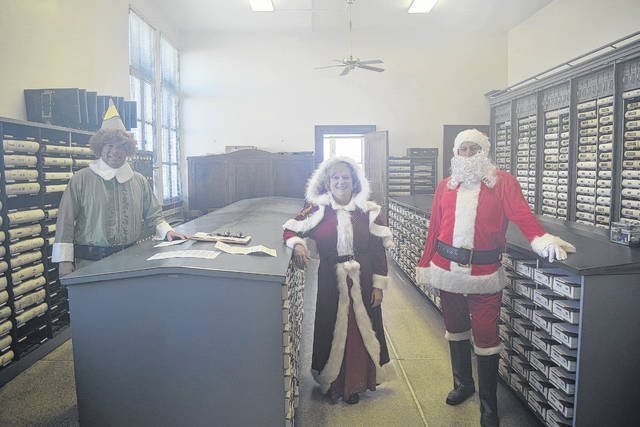 As Santa was too busy to come himself, Commission President Chris Day stood in for Santa, Commissioner Denise Robertson was Mrs. Claus, and Buddy the Elf loaned his clothes to Commissioner Rodney Creech.