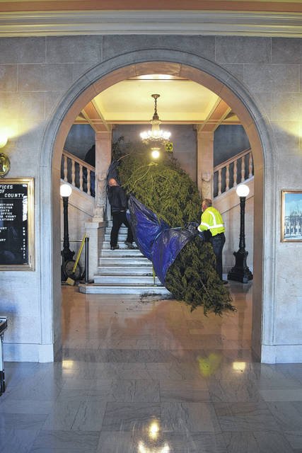 The Preble County Courthouse is now ready for the holiday season. First, the outside lights were turned on during Eaton's White Christmas celebration on Friday, Nov. 24, and now the inside is equally as festive. Preble County Commission President Chris Day helped move the giant tree to the second floor of the courthouse on Monday, Nov. 27, prior to the board of commissioners' meeting. He was helped by staff and prisoners from the Preble County Jail to chop, move, and position the tree.