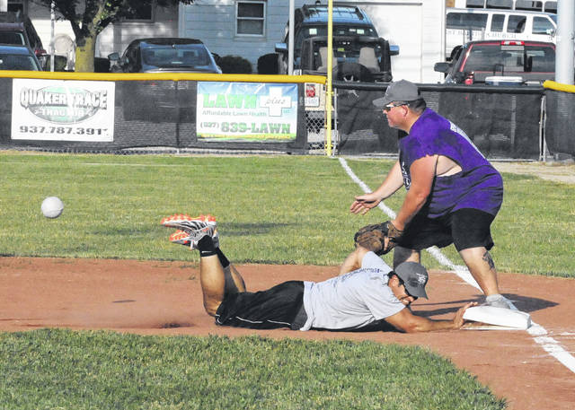 City of Eaton Police Chief Steve Hurd dives back into first base as Kevin Melling waits for the ball during the Leaders vs. Legends charity softball game on Friday, June 29.
